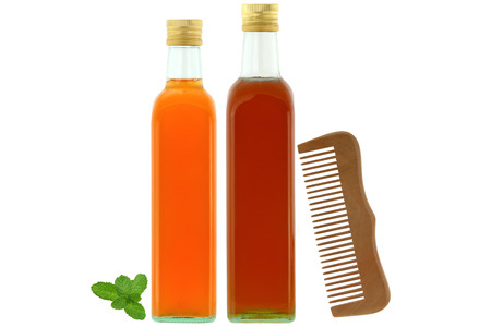 enzymes: Bottles of raw and unfiltered organic apple cider vinegar with mother enzymes, organic honey next to wooden comb, ingredients for dry and damaged hair treatment isolated on white background Stock Photo
