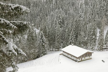 old barn in winter: Old wooden barn, farm house, in the mountain covered with snow in the forest during winter Stock Photo