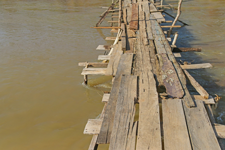 Simple weathered wooden bridge made to cross the river