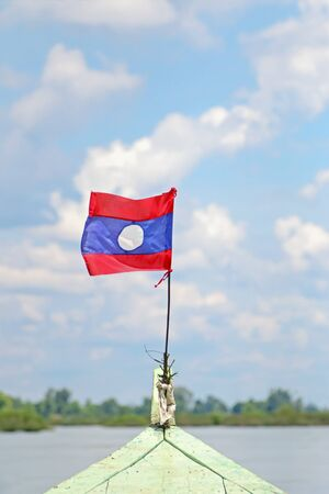 long tailed boat: Flag of Laos attached on long tailed boat with blurred background of the Mekong River in Laosflag, attach, pole, decorating, country,