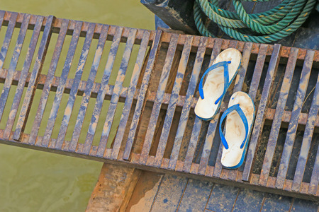 gangway: Wet dirt on white and blue rubber slippers on a portable metal gangway bridge connecting to the boat on Mekong River, Laos