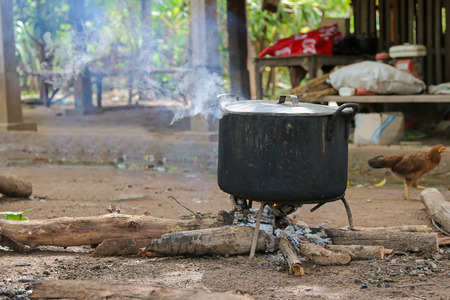 boiling pot: Hot steam coming out through lid on black boiling pot above wood fire on the ground in Laos