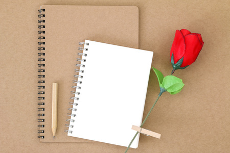 wooden pencil: Top view of blank notebook on natural brown paper next to wooden pencil and red rose