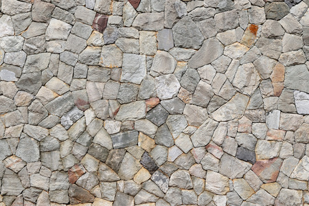 Background texture photo of stone wall made of mountain rocks, natural colors