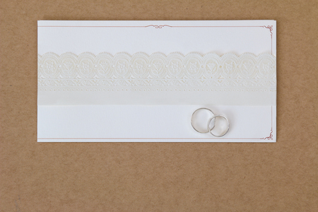 white ribbon: 2 rings on a wedding invitation card with white paper lace ribbon on brown paper background with copyspace