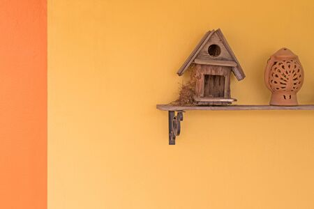 roosting: Oriental magpie robin bird build up its nest inside wooden bird house on a shelf against yellow wall
