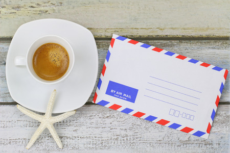 oversea: Starfish on freshly brewed espresso coffee next to blank classic air mail envelope