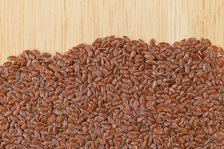 reddish: Reddish Brown seeds of Linseed, also called flaxseed on wooden background with copyspace. Flaxseed are seeds from flax plant