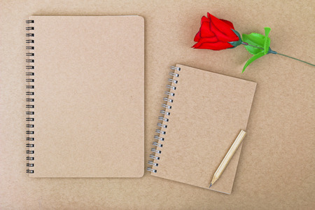 notebook cover: Top view of blank notebook on natural brown paper cover next to wooden pencil and red rose Stock Photo