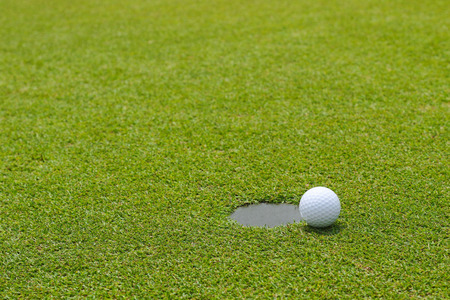 putting: Golf ball at the edge of putting cup hold at outdoor putting green