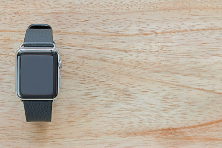 timekeeping: Smart watch with leather bands on wooden background with copyspace