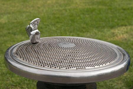provided: Public free drinking fountain tap, also called water bubbler, provided at the park with blurred green grass background in Melbourne, Australia