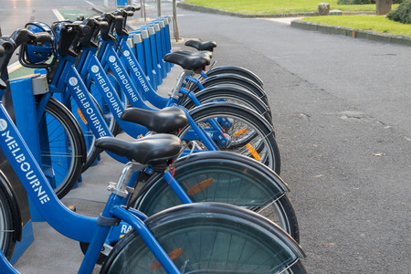 parking station: MELBOURNE, AUSTRALIA - APRIL, 2016 : Line of blue bicycles parking at the Melbourne Bike Share station in Melbourne, Australia on April 09, 2016. It is designed for short rides between stations within Melbourne, Docklands, South Melbourne and St Kilda. Editorial