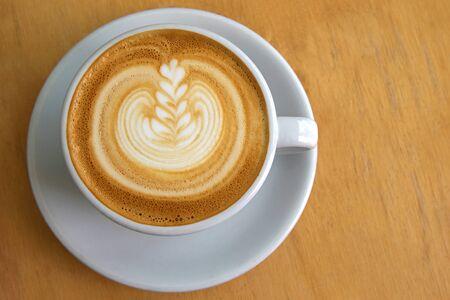 Tazza bianca di caffè caldo con decorazione di Latte Art sulla superficie, un tavolo di legno