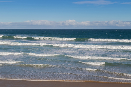 breaking waves: Morning view of the beach with breaking waves crashing sand on seashore, blurred background of blue sky in Victoria, Australia