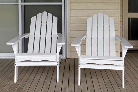 bungalow: Two white wooden adirondack chair on old weathered front porch at white bungalow Stock Photo
