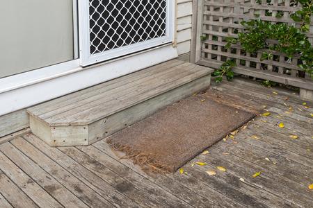 doorstep: Old plain coir doormat placing in front of the doorstep at back door during Autumn