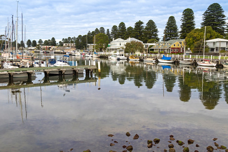 residential building: Boats moored next to beautiful modern houses along the Moyne River at Port Fairy in Victoria, Australia