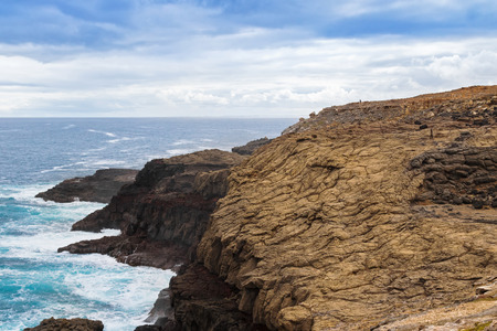 stoney: People walking on volcanic rocky promontory at blowholes, Cape Bridgewater in Victoria, Australia