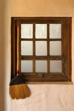 old styled: Old styled broom stick hanging by the wooden vintage window close to the entrance door to keep away bad folks and spirits