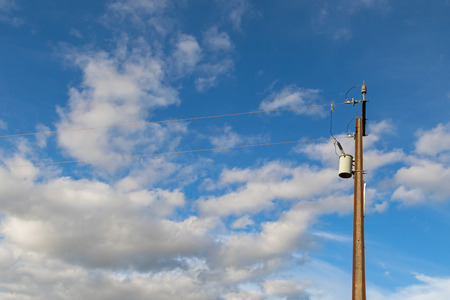 powers: Transformer on a electric power pole (utility pole) made of 2 steel joists against blue sky with copyspace, in South Australia Stock Photo
