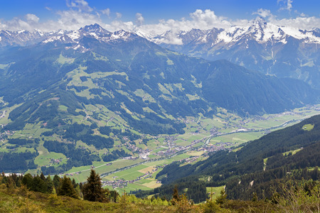 bird view: Bird view of the Zillertal valley village surrounded by mountains with snow during summer in Tyrol, Austria, Europe