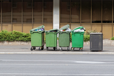 public waste: Group of over filled Wheelie bins, waste containers with wheel in green color full of trash on footpath in Adelaide, South Australia Stock Photo