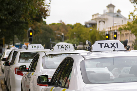 White taxi cars parking along the footpath in Adelaide, Australia with blurred background Standard-Bild