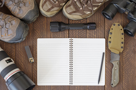 hiking shoes: Top view of blank notebook with dirty hiking shoes, Flashlight, knife, tele lens, binocular, matchstick. Set of travel accessories flatlay on wooden background