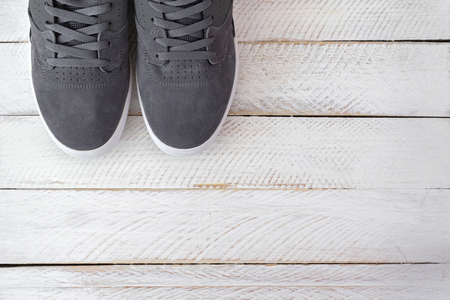 skateboard shoes: A pair of new stylish Skateboard shoes for men in grey color on white wooden background