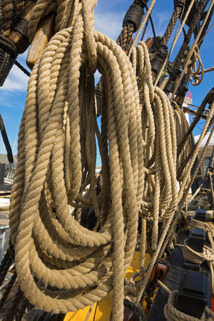 old ship: Closeup of rolled thick ropes on the old ship near wooden cleats