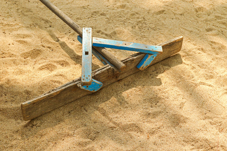 to flatten: Handmade wooden stick to flatten, level and smooth surface of sand on the beach   Stock Photo