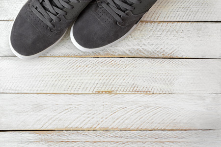 stylish men: A pair of new stylish Skateboard shoes for men in grey color on white wooden background