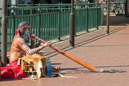 SYDNEY, AUSTRALIA - APRIL, 2016 : Busker sitting and blowing didgeridoo, Australian Aboriginal wind musical instrument, on the ground by the pier in Sydney, Australia on April 20, 2016.
