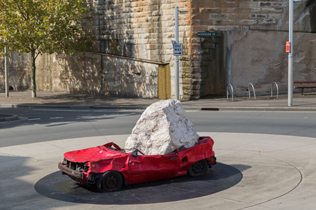 durham: SYDNEY, AUSTRALIA - APRIL, 2016 : Huge stone dropped on red car as outdoor sculpture called Still Life with Stone and Car, by American artist, Jimmie Durham, display at Pottinger Street roundabout in Sydney, Australia on April 20, 2016.