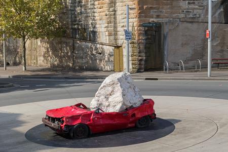 SYDNEY, AUSTRALIE - AVRIL, 2016: Une énorme pierre tombée sur une voiture rouge comme sculpture extérieure appelée Still Life with Stone and Car, de l'artiste américain Jimmie Durham, exposée au rond-point de la rue Pottinger à Sydney, en Australie, le 20 avril 2016.