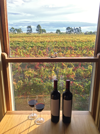 terroir: Glass of red wine next to bottles of wine near windows with soft view of vineyard in the afternoon. These wine grapes are growing on limestone coast in Coonawarra winery region during Autumn in South Australia