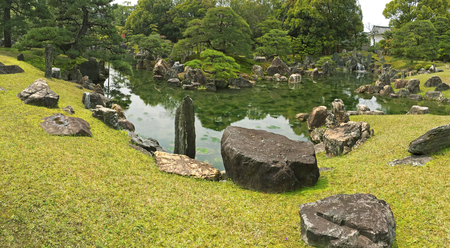 ornamental garden: Panoramic view of Ninomaru Garden with ornamental stones in a large pond. Panorama of traditional Japanese garden during spring in Kyoto, Japan