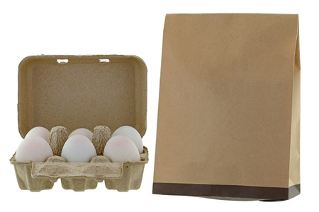 paperbag: Paper pulp egg tray packages of fresh eggs next to brown recycled paper bag isolated on white background