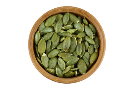 shelling: Top view of roasted pumpkin seeds in wooden bowl. Dry Pepita after shelling isolated on white background.