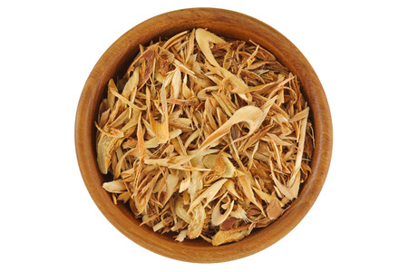 lemon grass: Top view of dried sliced Lemon grass to make tea, in wooden bowl isolated on white background.