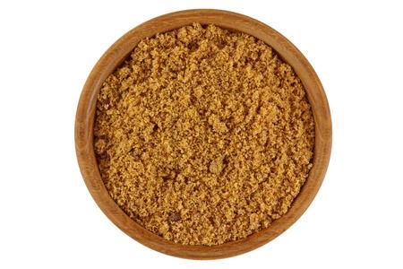 Draufsicht von nicht raffiniertem rohem natürlichem Brauner Zucker in der braunen Farbe in einer Holzschale isoliert auf weißen Hintergrund