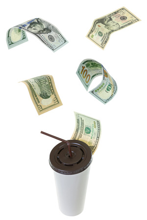 dinero volando: USD dollar banknote money flying above white paper cup for coffee with brown lid and straw isolated on white background