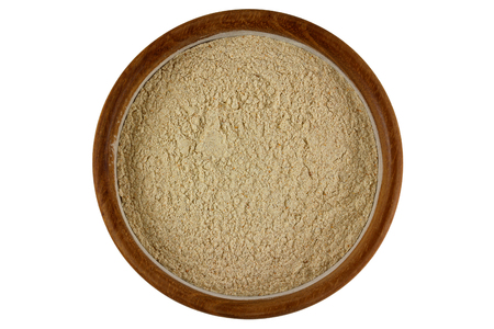 Top view of Herbal facial scrub in light brown color in a wooden bowl isolated on white background Stock Photo