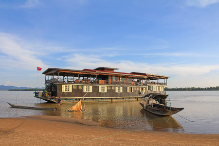 hulled: MEKONG, LAOS - MAY 2015 : Wooden boat in front of The Vat Phou Cruise 2 decks floating hotel, steel hulled teak barge, on Mekong River, Southern Laos on May 24, 2015.