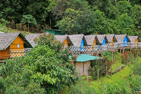 house with style: Colorful Thai styled wooden hut with thatched roof surrounded by forest in Mon Jam, Chiang Mai, Thailand