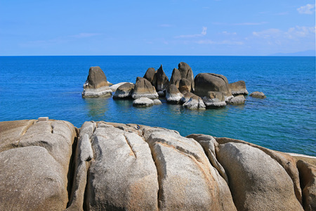 Closeup of rocks at rocky seashore against blue sea water and sky at Koh Samui Island in Surat Thani province, Thailand