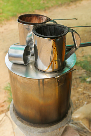 tea filter: Pot of hot water boiler on wood fueled stove with coffee filter strainer bag. Traditional way to make Laos styled coffee called Kafe Lao and tea Stock Photo