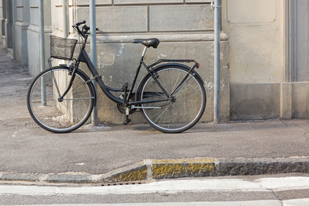 old styled: Old styled Bicycle with basket parking near street. Chained black bike in the corner outside the building. Stock Photo