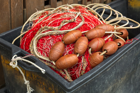 Plastic box full of red white fishing net, huge floats, nylon rope used in fishing industry Stock Photo